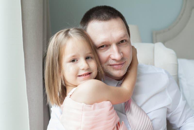 Padre e figlia che stringono a sé a casa fotografia stock