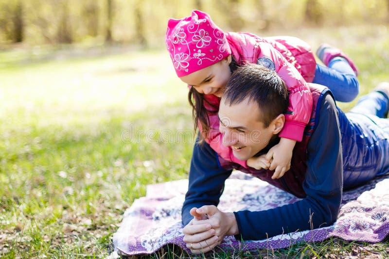 Padre e figlia devoti sdraiati sull'erba, godersi l'una l'altra compagnia, legarsi, giocare, divertirsi in natura su una luminosa fotografia stock