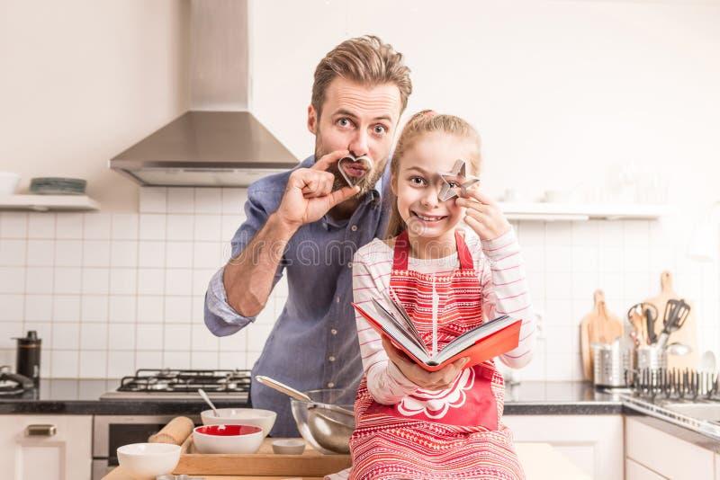 Padre e figlia divertendosi nella cucina - cottura immagine stock
