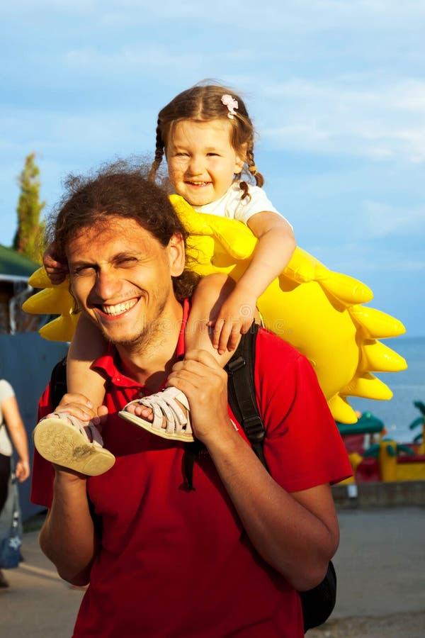 Padre e figlia. Fare da baby-sitter sulle spalle del papà immagini stock libere da diritti