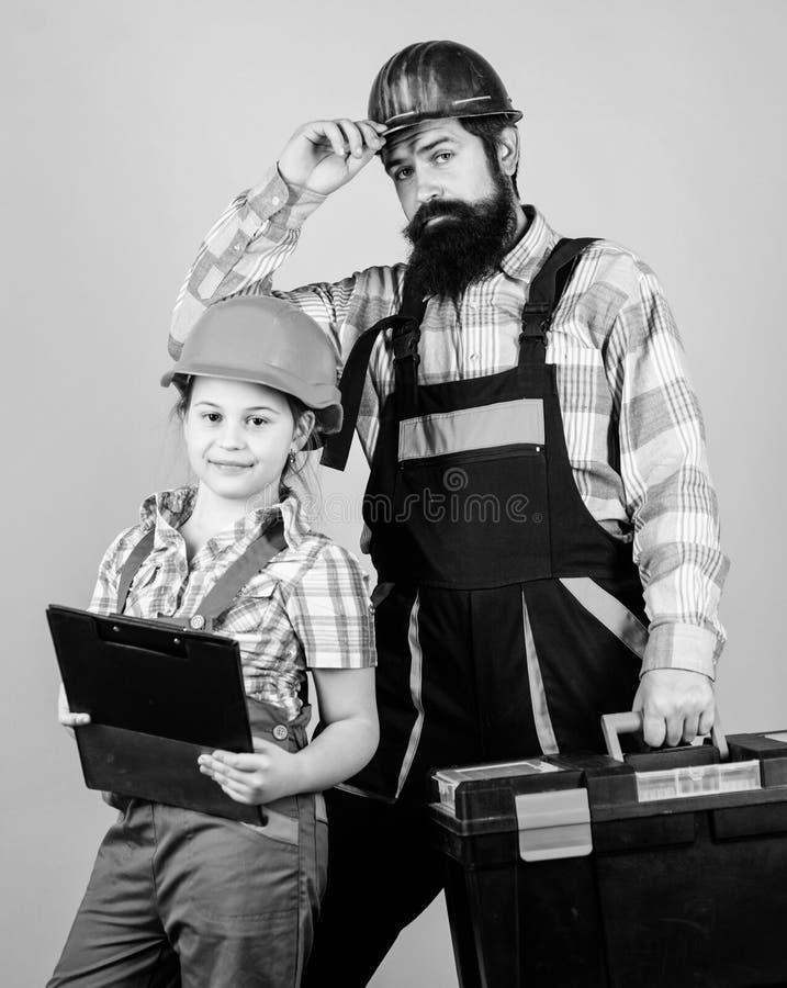 Padre e figlia in officina Riparatore in uniforme engineer Uomo barbuto con la bambina Operaio di costruzione immagine stock