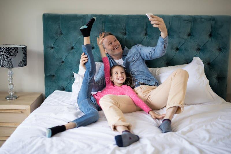 Padre e figlia sorridenti che prendono selfie con il telefono cellulare sul letto immagine stock libera da diritti