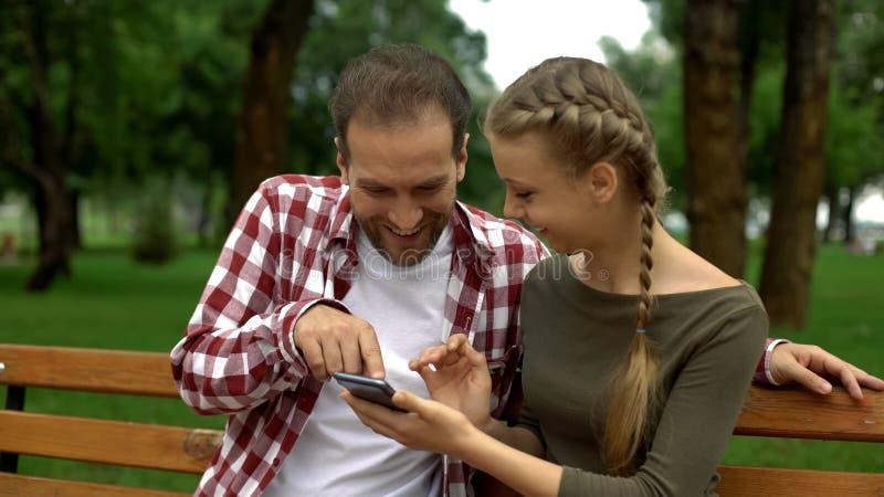Padre e figlia sorridenti che ridono della foto divertente del parente sullo smartphone immagine stock libera da diritti