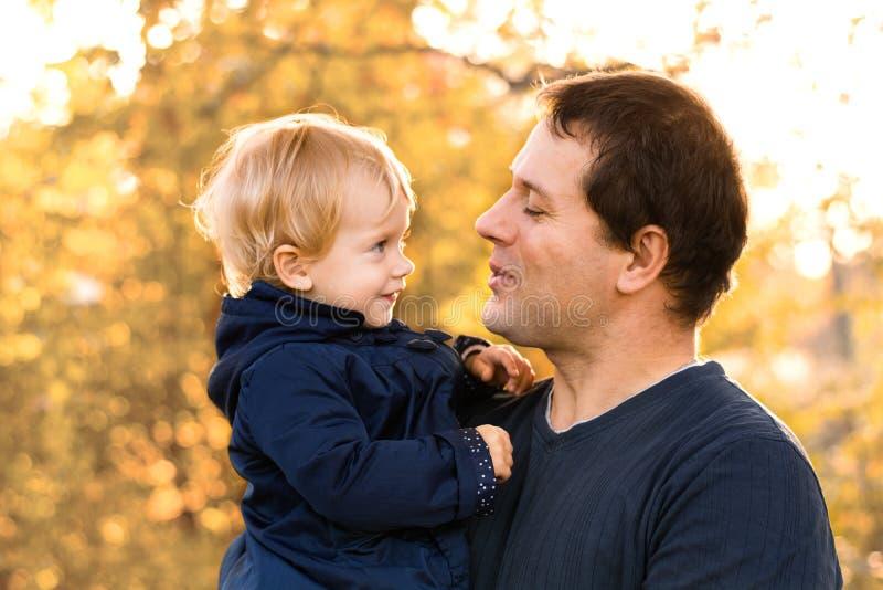 Padre e figlia in vestiti blu nella foresta gialla di autunno immagine stock