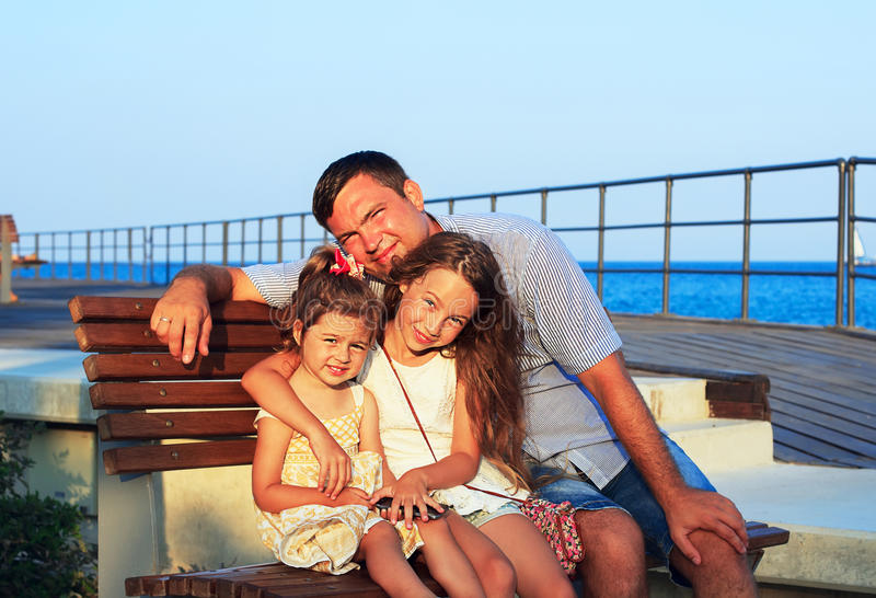 Padre e figlie che giocano insieme alla spiaggia al tramonto Ha fotografie stock