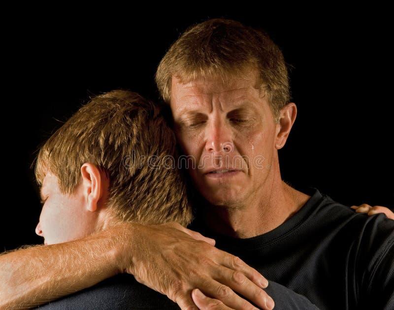 Padre e figlio, abbraccio lacrimoso immagine stock