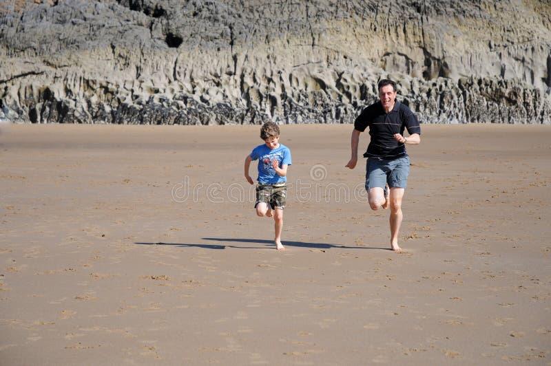 Padre e figlio che corrono sulla spiaggia fotografia stock