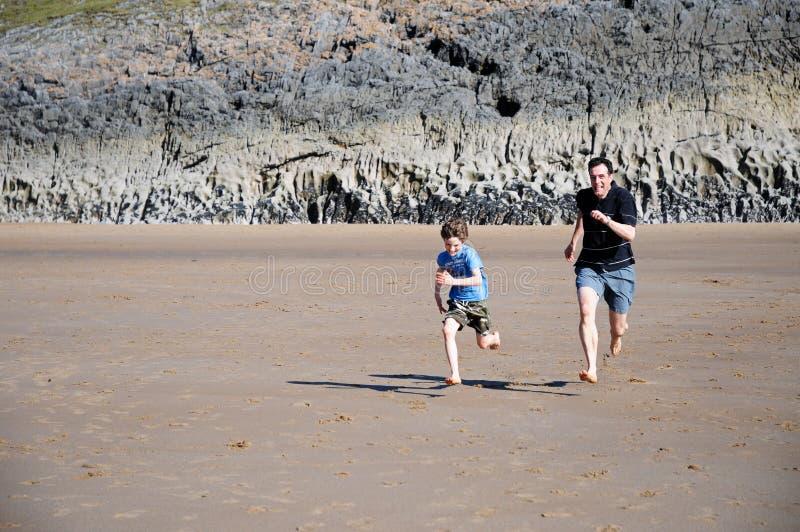 Padre e figlio che corrono sulla spiaggia fotografia stock libera da diritti
