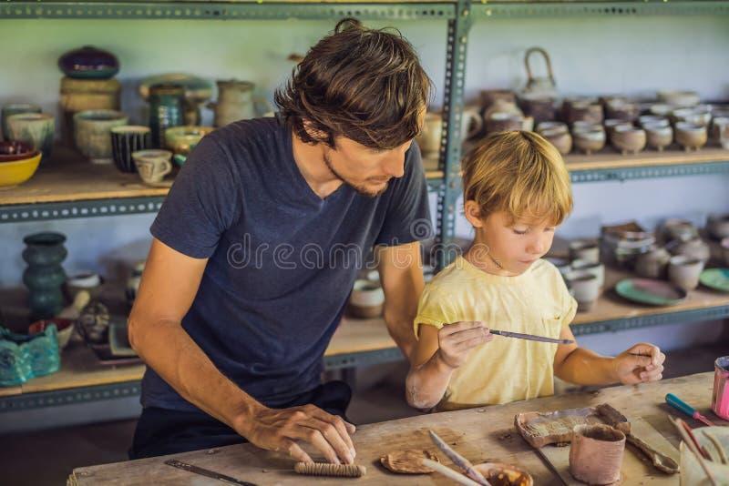 Padre e figlio che fanno vaso ceramico nell'officina delle terraglie fotografie stock