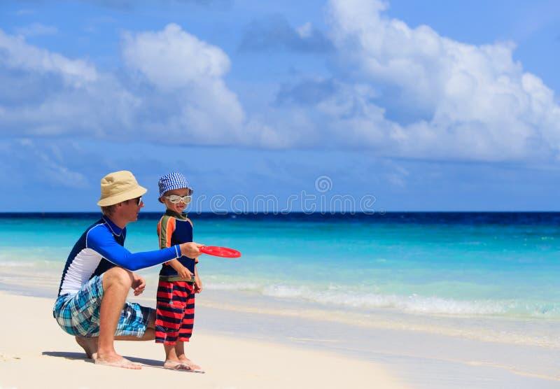 Padre e figlio che giocano con il disco di volo alla spiaggia fotografia stock libera da diritti