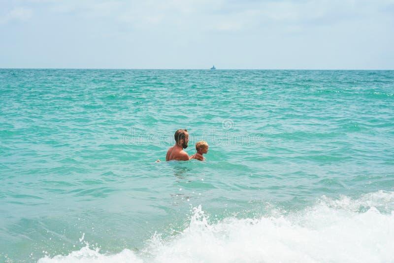 Padre e figlio che giocano nel mare fotografia stock