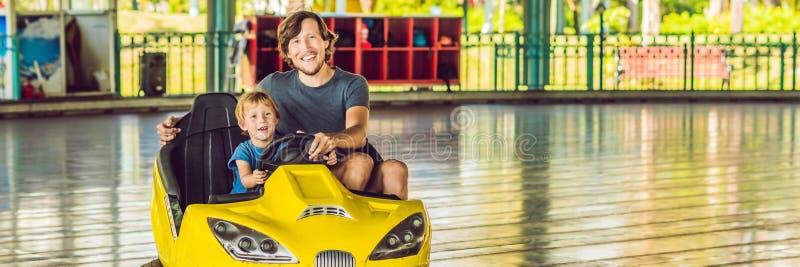 Padre e figlio che hanno un giro nell'automobile di paraurti all'INSEGNA del parco di divertimenti, formato lungo fotografie stock libere da diritti