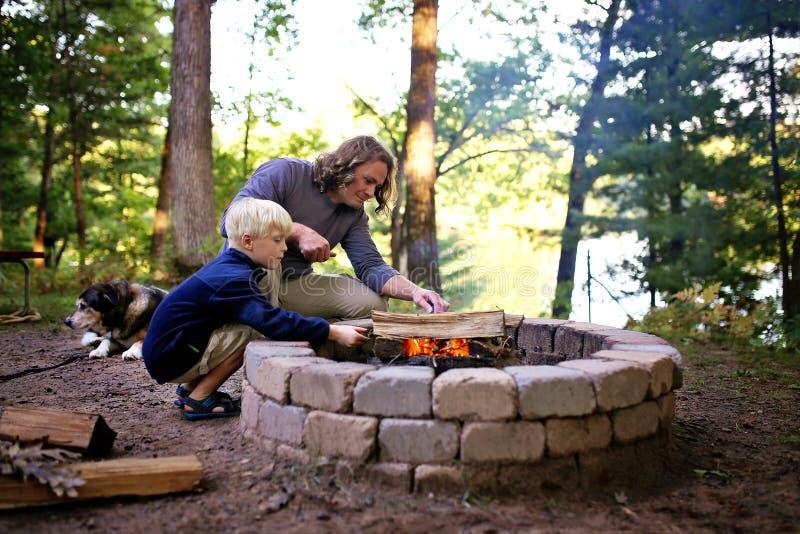 Padre e figlio che iniziano fuoco di accampamento in anello del fuoco al campeggio che trascura un lago nel legno immagine stock libera da diritti