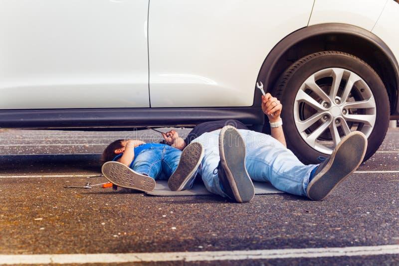 Padre e figlio che lavorano insieme sotto l'automobile rotta immagine stock libera da diritti