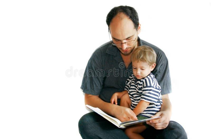 Padre e figlio che leggono un libro fotografia stock