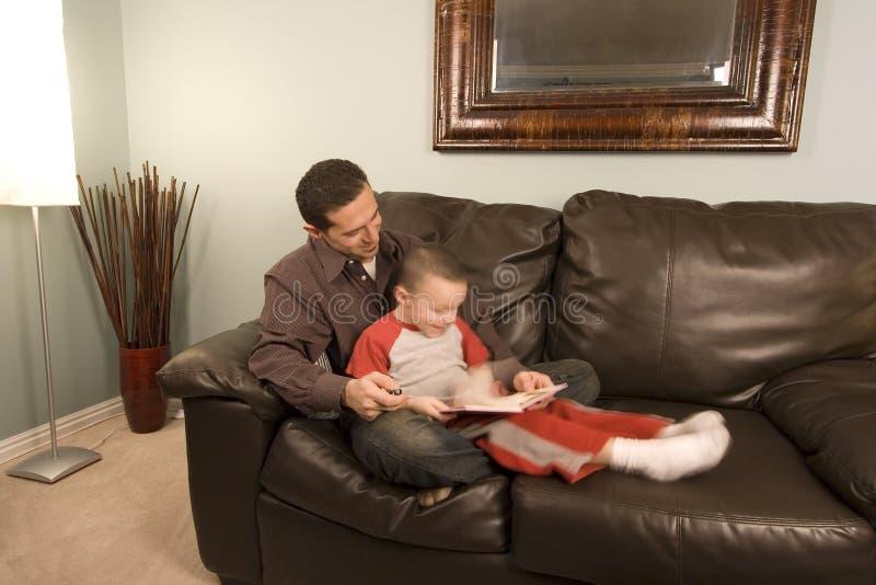 Padre e figlio che leggono un libro sullo strato fotografie stock