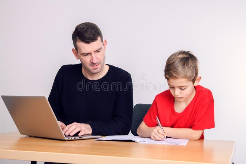 Padre e figlio che per mezzo insieme del computer fotografia stock