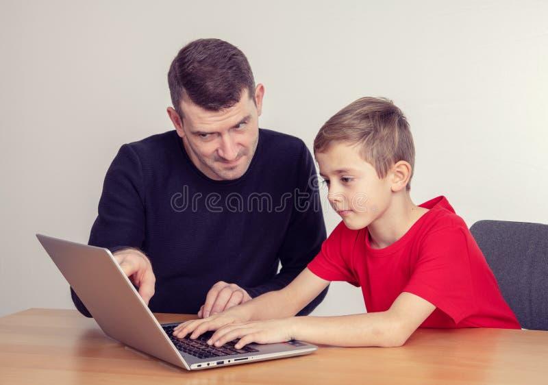 Padre e figlio che per mezzo insieme del computer immagini stock libere da diritti