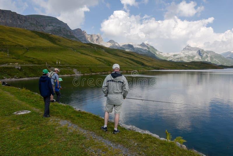 Padre e figlio che pescano insieme nel lago Tannensee sulla Svizzera fotografie stock