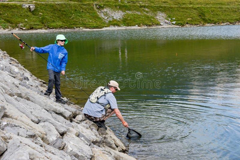 Padre e figlio che pescano insieme nel lago Tannensee sulla Svizzera immagine stock libera da diritti