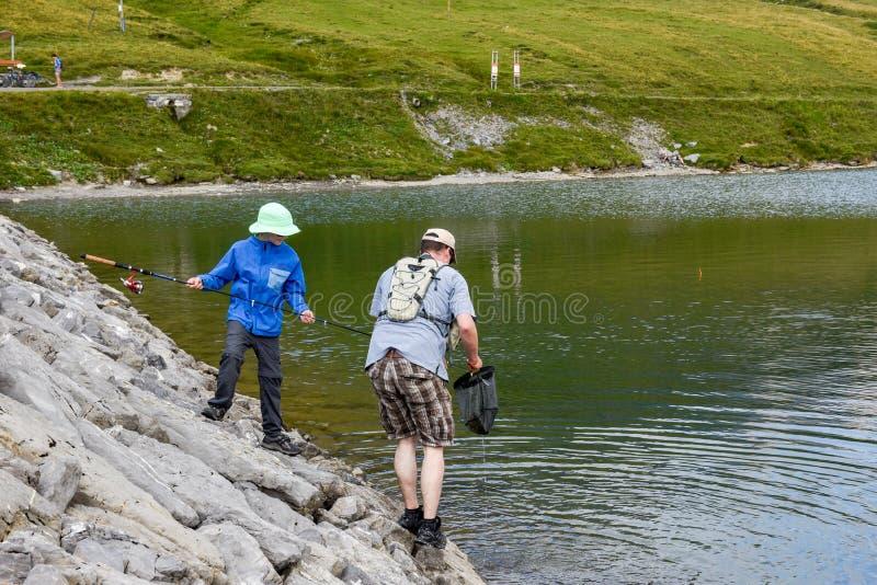 Padre e figlio che pescano insieme nel lago Tannensee sulla Svizzera fotografia stock libera da diritti