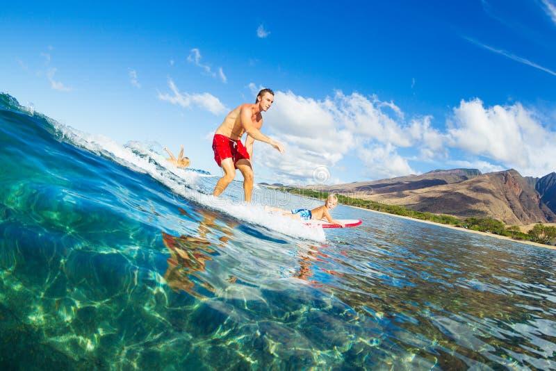 Padre e figlio che praticano il surfing insieme, Wave di guida immagine stock