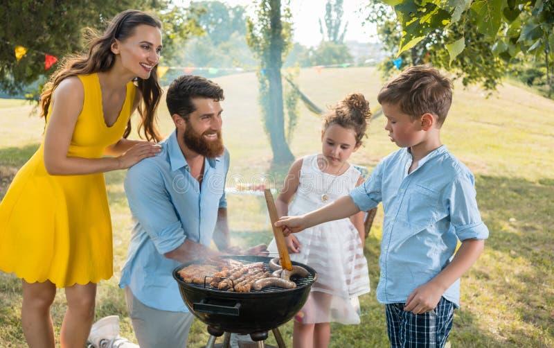 Padre e figlio che preparano carne sulla griglia del barbecue del carbone fotografie stock libere da diritti