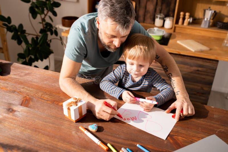Padre e figlio che rendono a biglietti di S. Valentino carta per la madre immagini stock