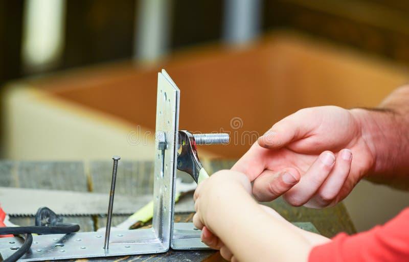 Padre e figlio che riparano insieme, vicino su Concetto di assistenza e di riparazione Aiuti della mano di Childs adulti torcere  fotografia stock