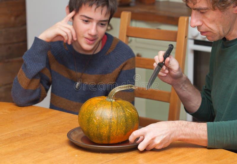 Padre e figlio che scolpiscono la zucca di Halloween su un tavolo da cucina immagini stock