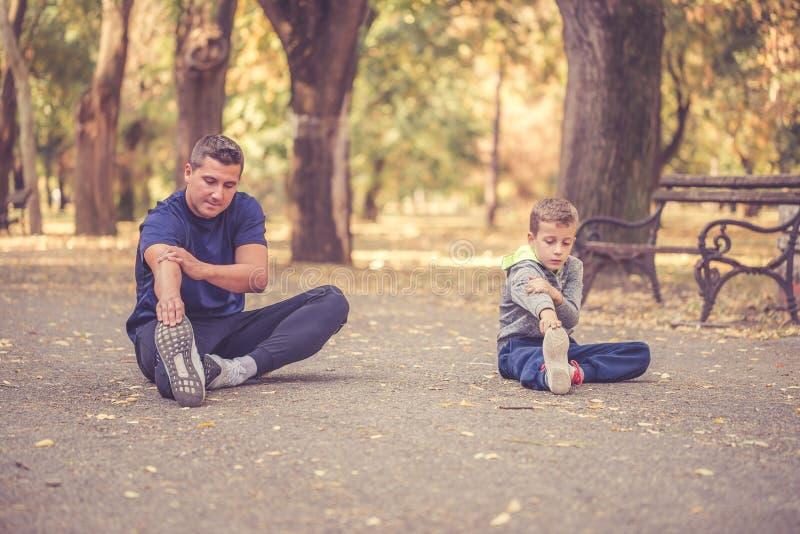 Padre e figlio che si esercitano insieme all'aperto fotografia stock