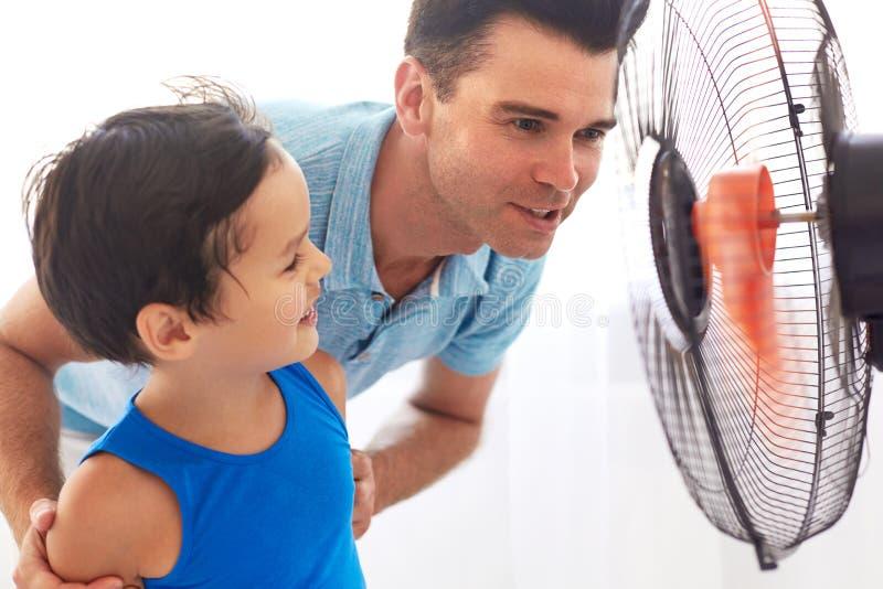 Padre e figlio che si raffreddano davanti al fan Giorno caldo fotografie stock