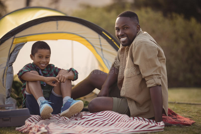 Padre e figlio che si siedono su una coperta in parco immagine stock libera da diritti