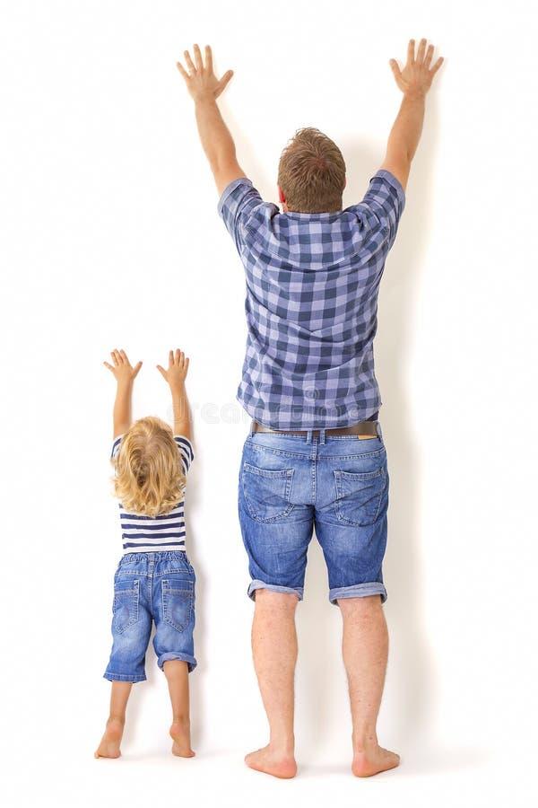 Padre e figlio che stanno con le loro parti posteriori alla macchina fotografica fotografia stock