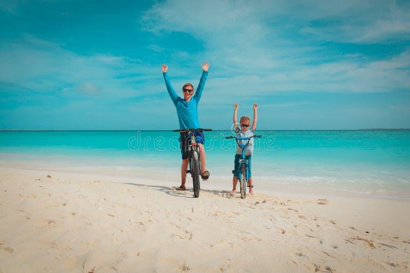 Padre e figlio e ciclismo felici sulla spiaggia immagini stock