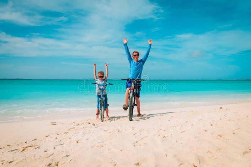 Padre e figlio e ciclismo felici sulla spiaggia fotografie stock libere da diritti