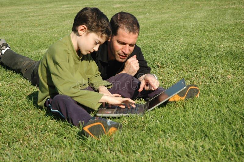 Padre e figlio con il computer portatile immagini stock