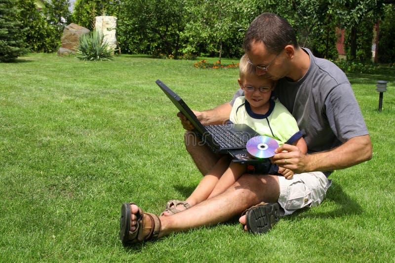 Padre e figlio con un computer fotografia stock libera da diritti