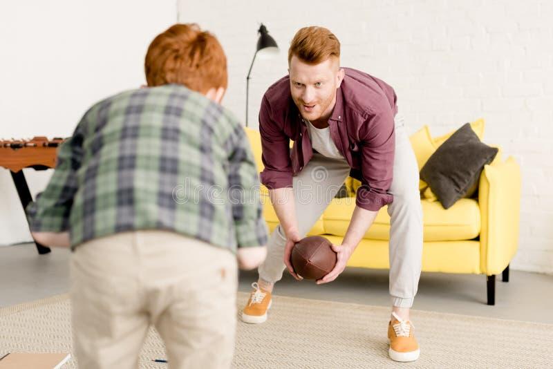 padre e figlio dai capelli rossi sorridenti che giocano con la palla di rugby fotografia stock libera da diritti