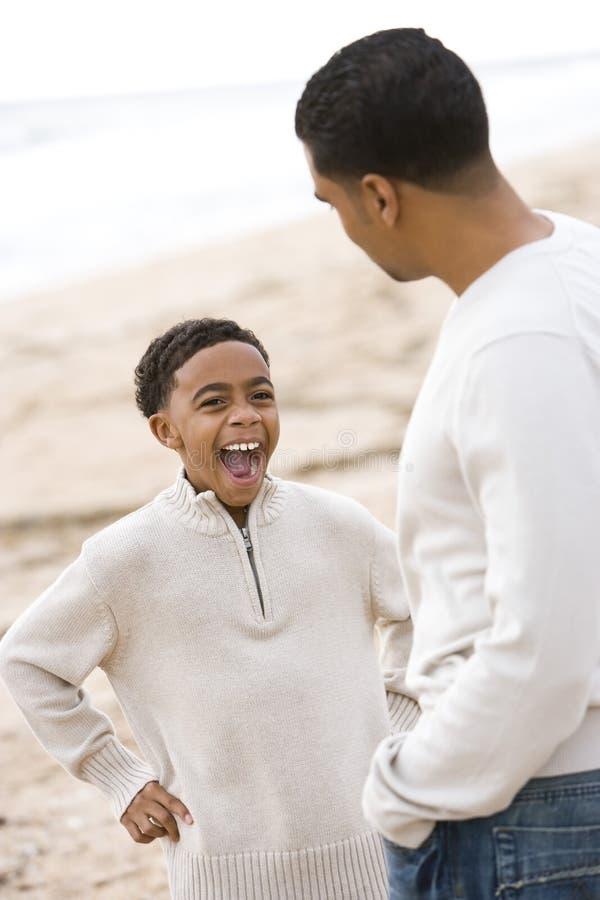 Padre e figlio del African-American che giocano sulla spiaggia fotografia stock