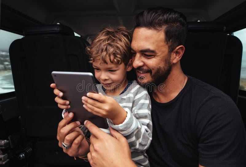 Padre e figlio felici sul viaggio stradale facendo uso della compressa digitale fotografia stock