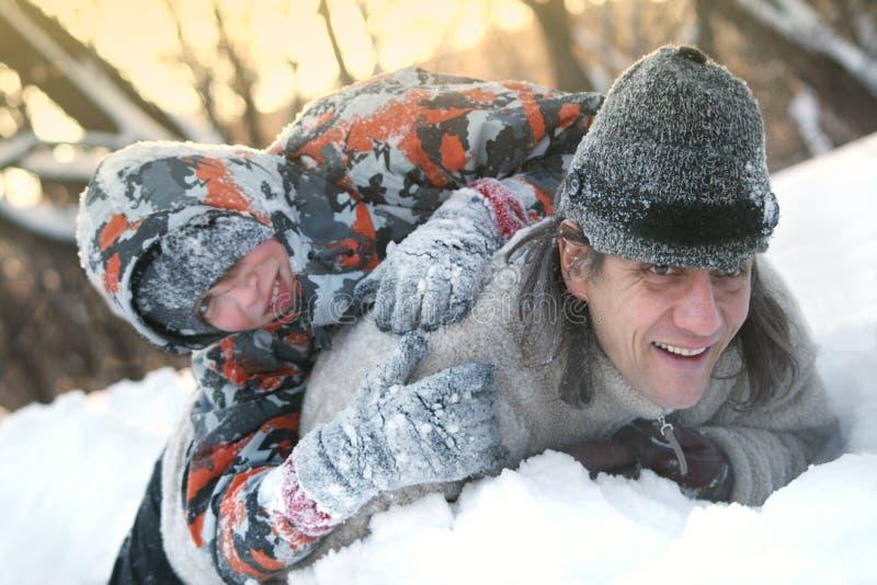 Padre e figlio nell'inverno su un laminare a freddo e gioco nella neve immagini stock