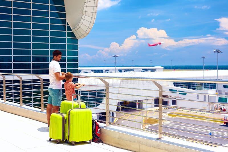 Padre e figlio pronti per le vacanze estive, mentre aspettando imbarco nell'aeroporto internazionale immagini stock