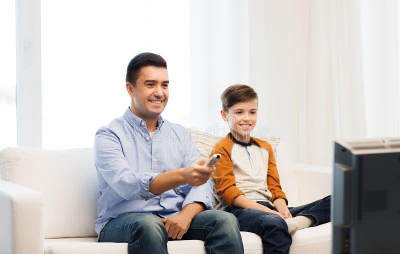 Padre e figlio sorridenti che guardano TV a casa immagini stock