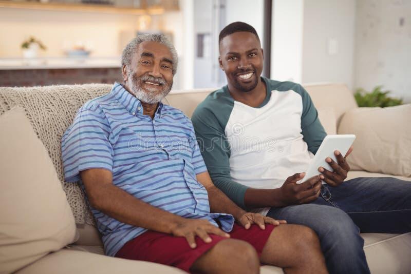Padre e figlio sorridenti che si siedono sul sofà con la compressa digitale in salone immagine stock