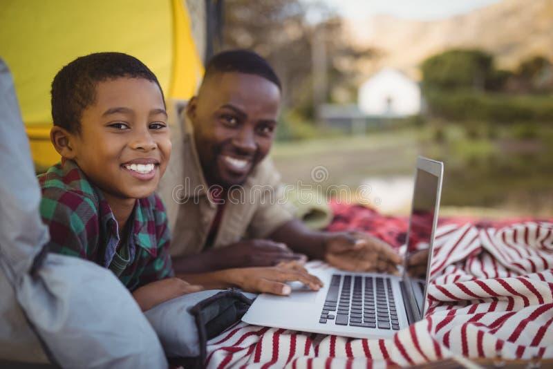 Padre e figlio sorridenti che utilizza computer portatile nella tenda fotografia stock