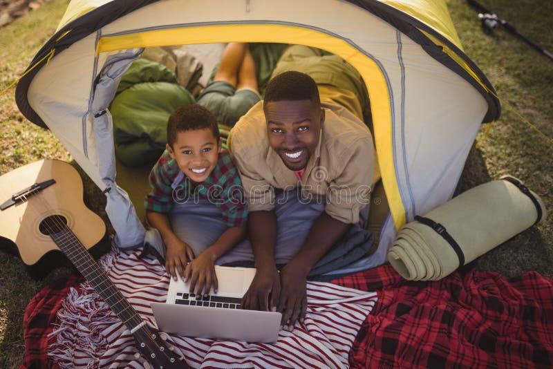 Padre e figlio sorridenti che utilizza computer portatile nella tenda immagine stock