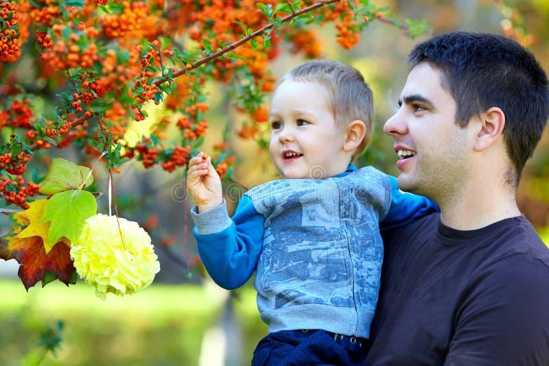 Padre e figlio sorridenti sulla priorità bassa di autunno immagine stock