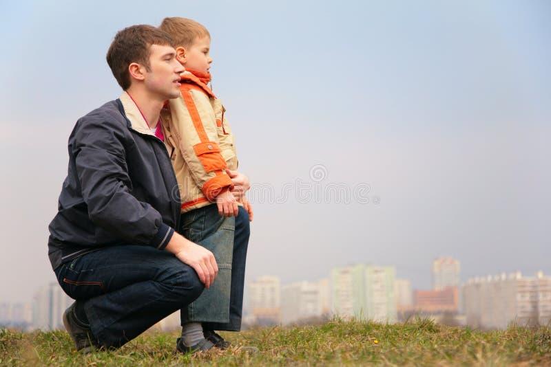 Padre e figlio su erba. città immagine stock libera da diritti