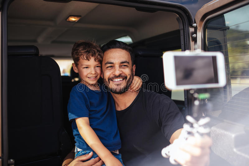 Padre e figlio sul viaggio stradale che prende selfie fotografia stock libera da diritti